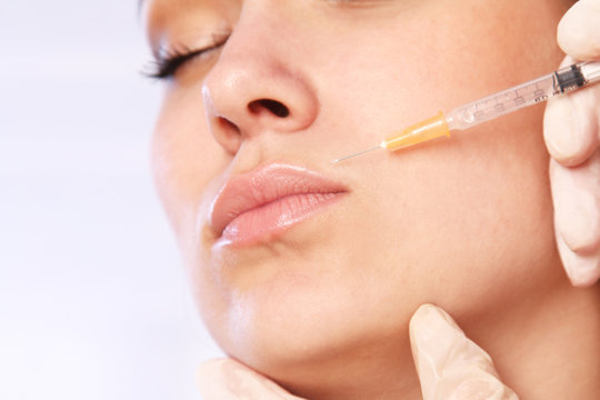 Close-up young woman receives cosmetic injection with syringe