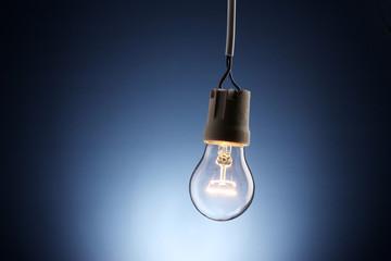 lit light bulb on blue background