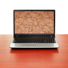 Notebook on the table showing cracked clay ground on the screen