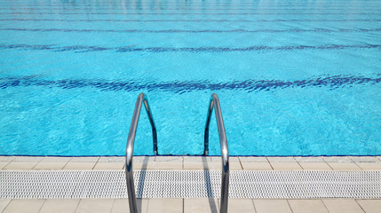 Swimming pool steel ladder and clear blue water