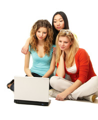 Three girls sitting on the floor with a laptop