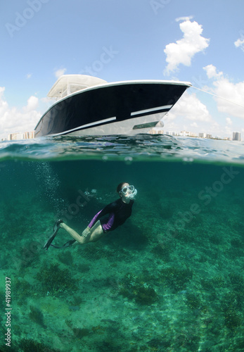 Wall mural fit young woman snorkeling underwater