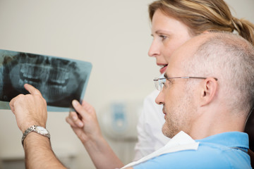patient und zahnärztin sprechen über röntgenbild
