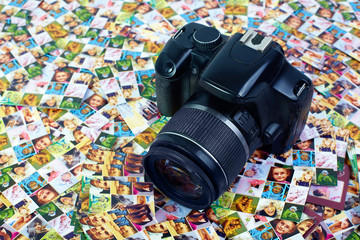 photo bussiness. SLR camera lying on huge number of digital prin