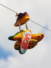 Worn sneakers with graffiti hanging on a rope