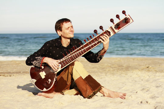Man playing the sitar near the sea