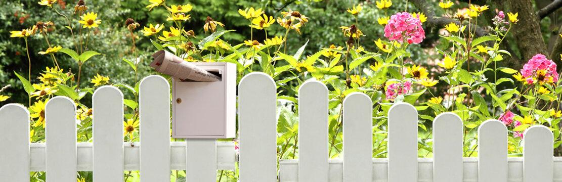 Gartenzaun mit Briefkasten und Zeitung