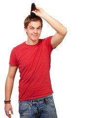 portrait of young man cutting his hair over white background