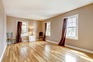 Empty large room with three windows and hardwood.