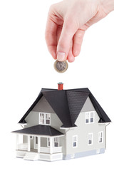 Hand putting coin into house architectural model