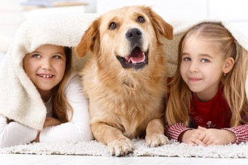 Little sisters and pet dog at home smiling