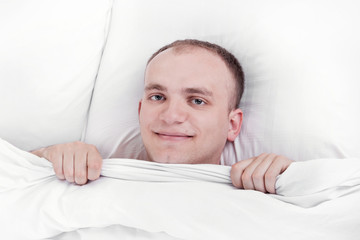 handsome man in bed at home with a pleased and smiling face