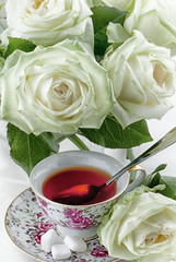 Cup of tea and white roses
