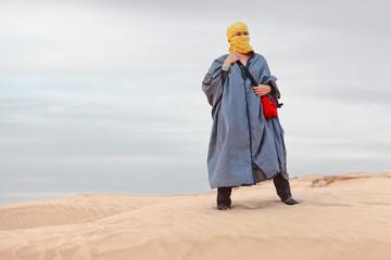 Woman in bedouin clothes standing on dune in desert
