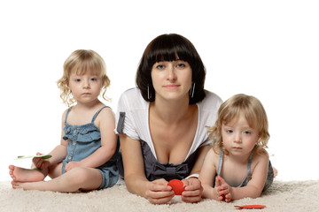 Mother with her two daughters twins lying down on the floor