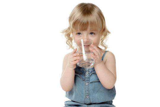 Lovely little girl drinking water, over white