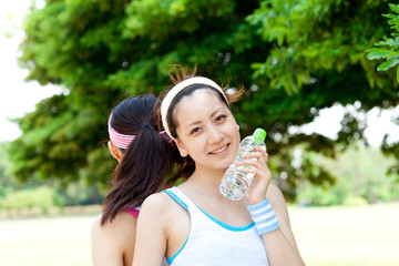Beautiful young women drinking water at workout. Portrait of asi