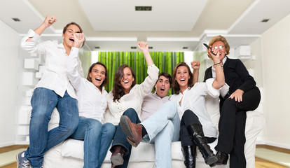 Family in modern interior watching a winning match