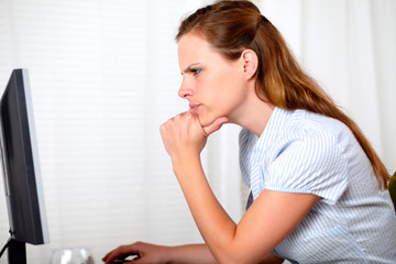 Charming pensive pretty girl looking on computer