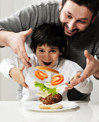 Kid and father making burger together