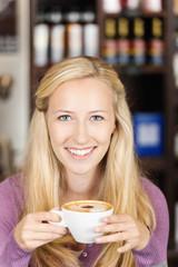 blonde frau mit einer tasse cappuccino
