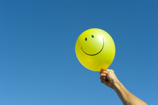 Arm with happy smiley balloon