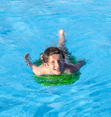 boy relaxing on a surfboard in the pool