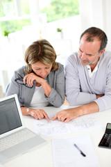 Senior couple reading construction plan in office