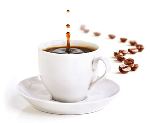 Foto op Aluminium Koffiebonen A cup of coffee with a splash of drops and coffee beans.
