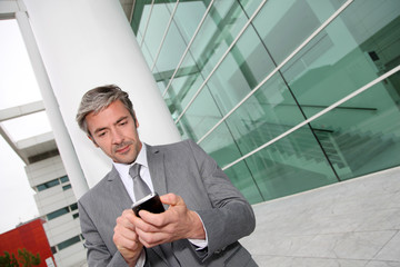 Businessman writing short message on mobile phone