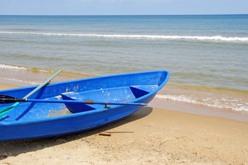 Blue boat on a sandy beach against the sea