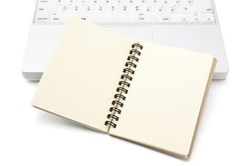 開いたメモ帳とノートパソコン