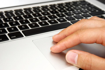 male hand with touchpad on laptop