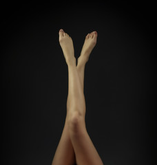 Long  woman's legs  crossed isolated on black background