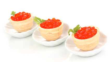 Red caviar in tartlets on little white saucers isolated on white