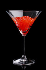 Red caviar in glass isolated on black