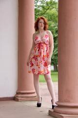 Frau im Sommerkleid zwischen Säulen