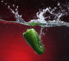 Green pepper falling into water. Red background