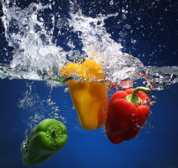 Three peppers falling into water. Blue background