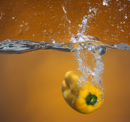 Yellow pepper falling into water. Background in the same tone