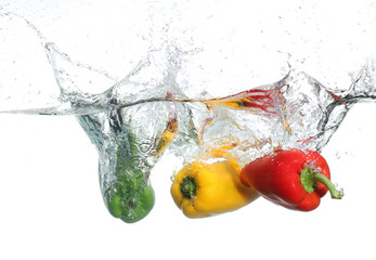 Three peppers falling into water, over white background