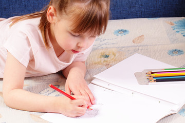Beautiful little girl draws funny picture
