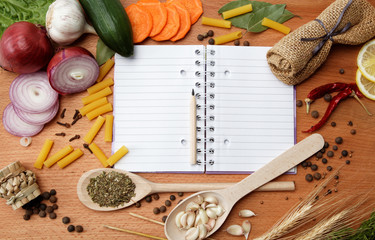 notebook for recipes and spices on wooden table