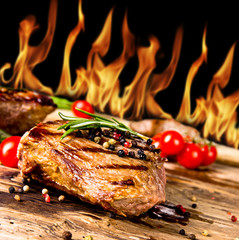Grilled beef steaks with flames on background - fototapety na wymiar