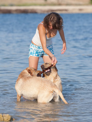 Young woman playing with a couple of dogs in the sea