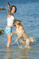 Girl playing with dog at the sea