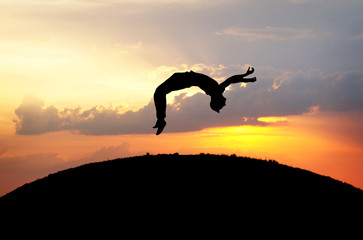 Wall Mural - silhouette of gymnast jumping on hill in sunset