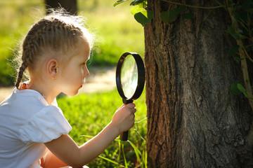 Little girl examining tree stem through the magnifying glass