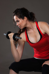 Beautiful young  woman lifting weights