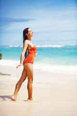 Young beautiful wet woman sitting on the sand near ocean, Bali,